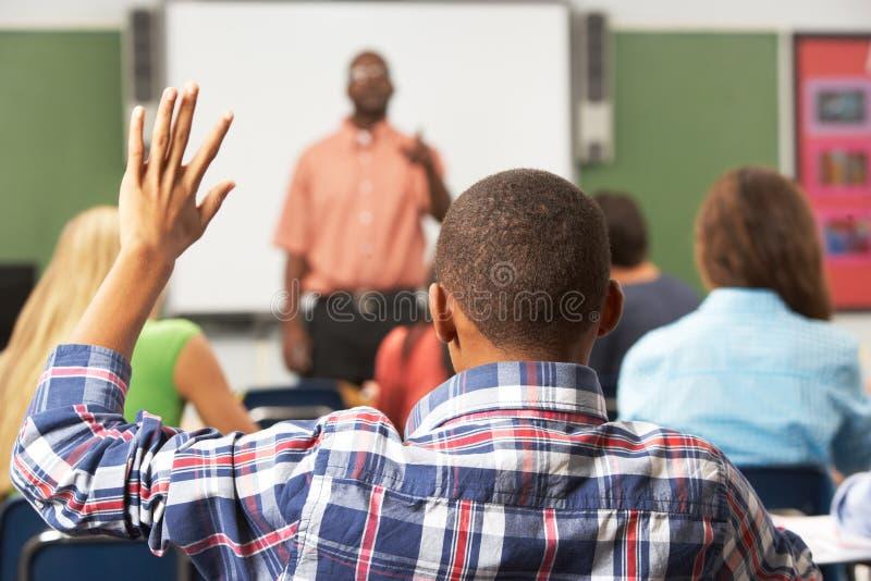 Alumno masculino que aumenta la mano en clase fotografía de archivo libre de regalías