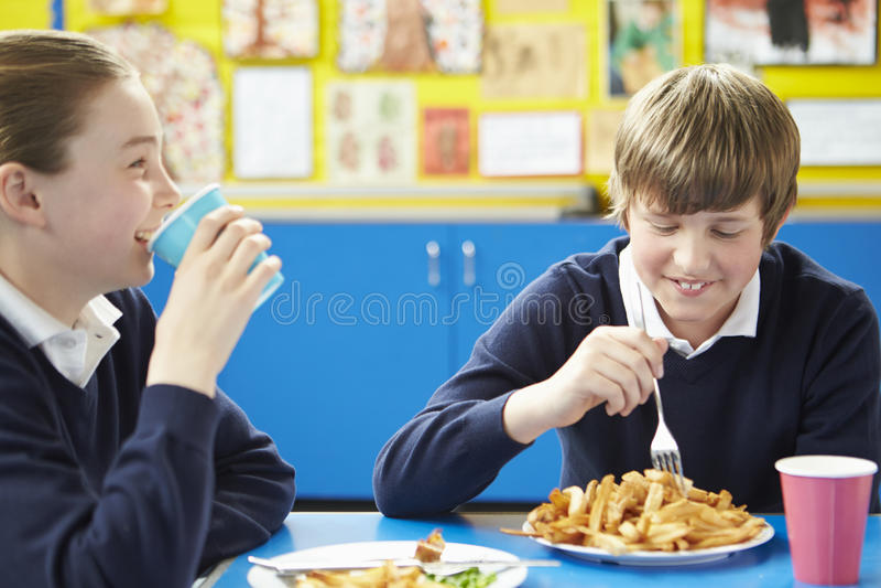 Alumno masculino que come el almuerzo escolar malsano foto de archivo libre de regalías