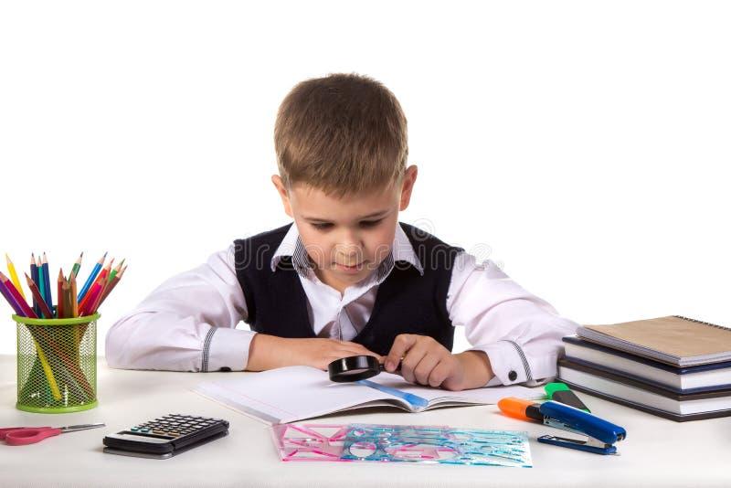 Alumno serio elegante en el escritorio que explora con la lupa en el fondo blanco limpio foto de archivo libre de regalías