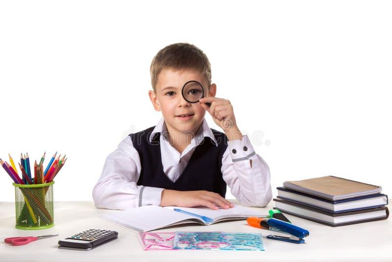 Alumno serio elegante en el escritorio que sostiene la lupa cerca del ojo en el fondo blanco limpio imagen de archivo