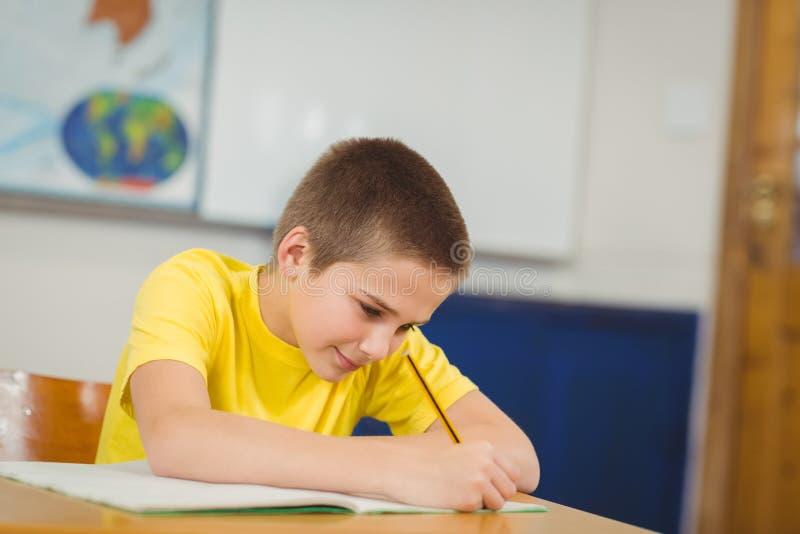 Alumno sonriente que trabaja en su escritorio en una sala de clase foto de archivo libre de regalías