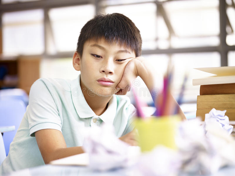 Alumno triste que se sienta solamente en sala de clase imagen de archivo