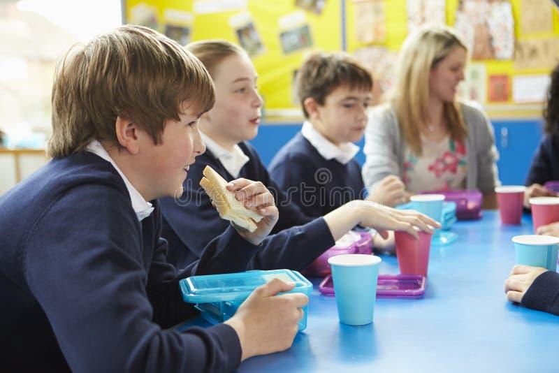 Alumnos con el profesor Sitting At Table que come el almuerzo foto de archivo