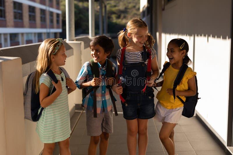 Alumnos con las carteras que hablan con uno a en vestíbulo fotos de archivo libres de regalías