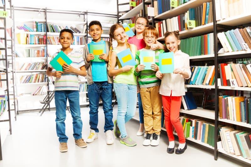 Alumnos con los cuadernos en biblioteca fotos de archivo