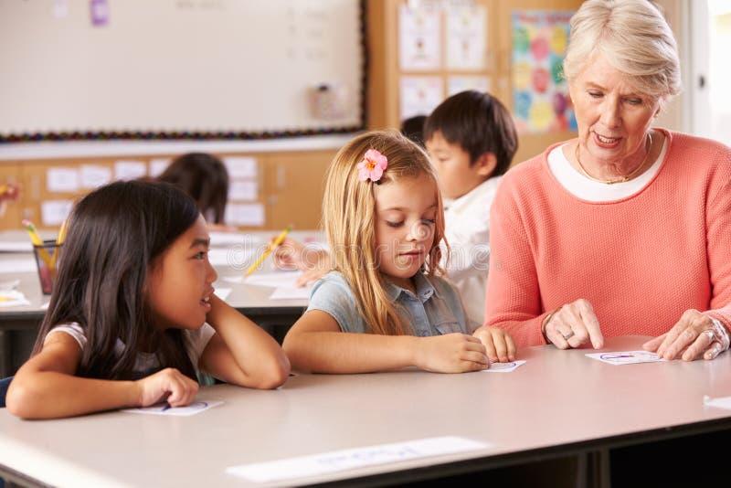 Alumnos de ayuda del profesor mayor en la lección de la escuela primaria imagen de archivo libre de regalías