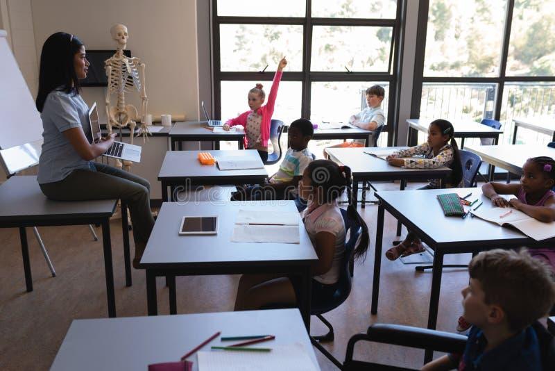 Alumnos de enseñanza del profesor de escuela de sexo femenino en el ordenador portátil en sala de clase fotos de archivo libres de regalías