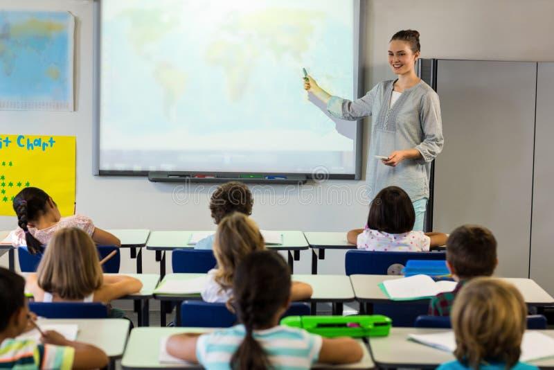 Alumnos de enseñanza del profesor que usan la pantalla de proyector foto de archivo