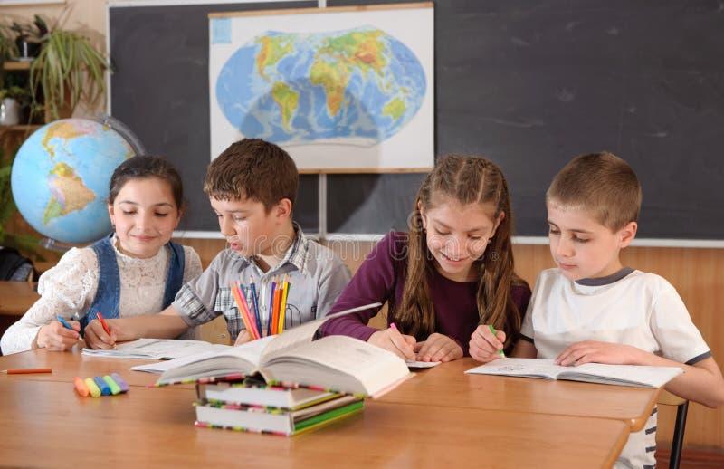 Alumnos de Fout en el lessin de la geografía en la escuela primaria imagen de archivo