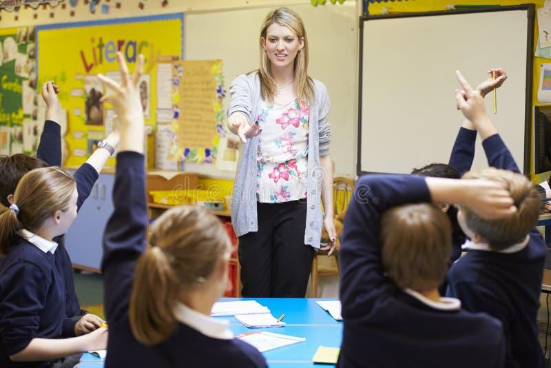 Alumnos de la escuela primaria de Teaching Lesson To del profesor fotos de archivo