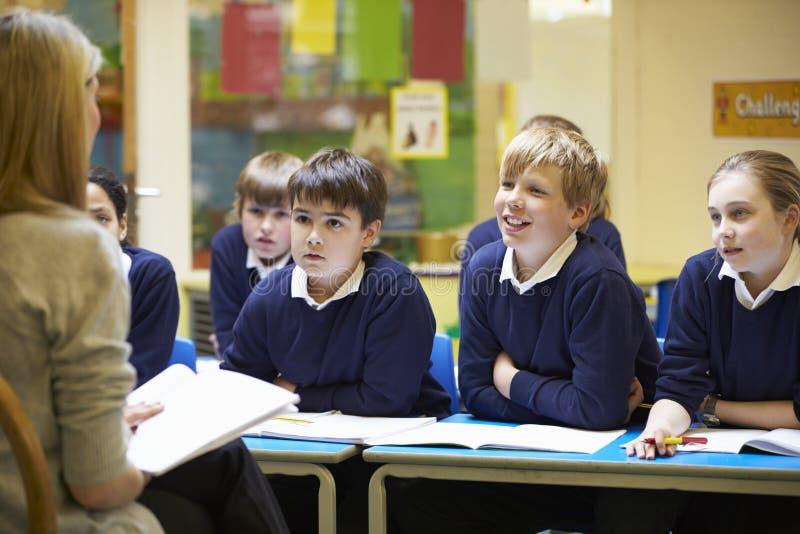 Alumnos de la escuela primaria de Teaching Lesson To del profesor imagen de archivo