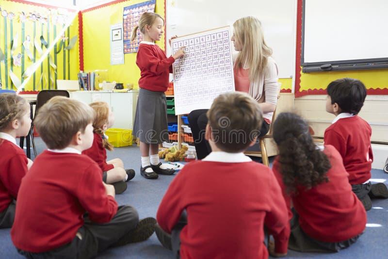 Alumnos de la escuela primaria de Teaching Maths To del profesor fotografía de archivo libre de regalías