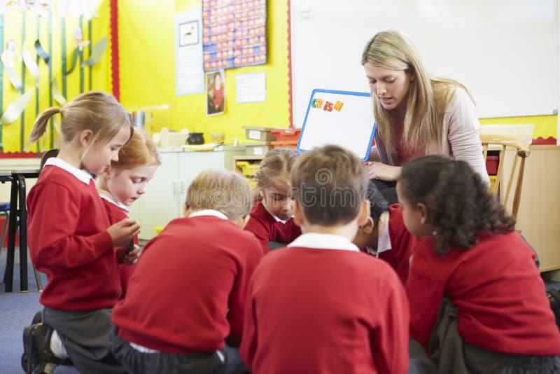 Alumnos de la escuela primaria de Teaching Spelling To del profesor fotografía de archivo