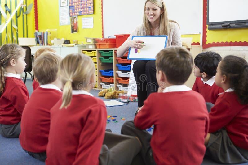 Alumnos de la escuela primaria de Teaching Spelling To del profesor fotos de archivo
