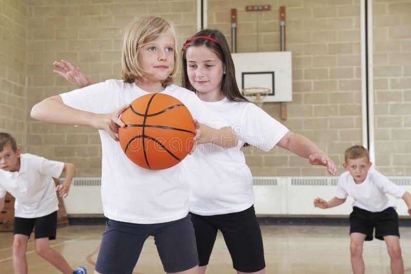 Alumnos de la escuela primaria que juegan a baloncesto en gimnasio imagen de archivo