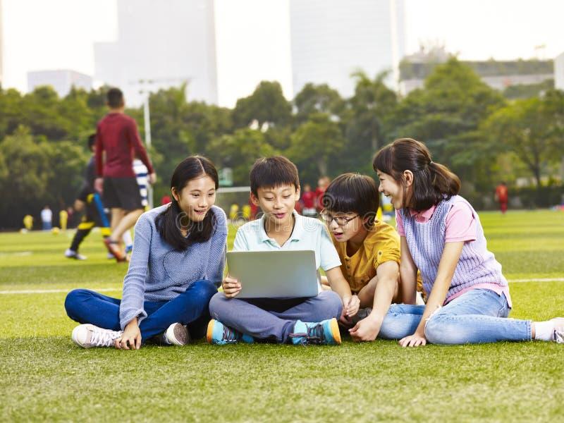 Alumnos elementales asiáticos que usan el ordenador portátil al aire libre imagenes de archivo