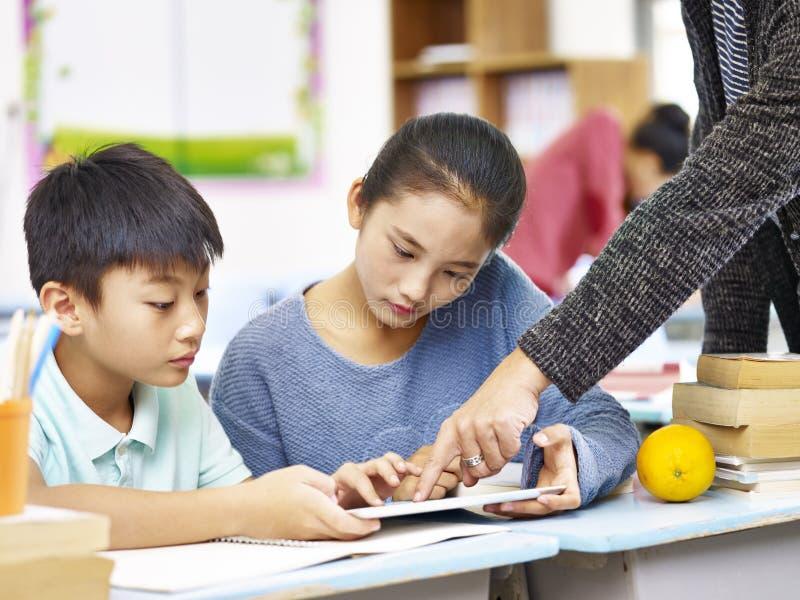 Alumnos elementales asiáticos que usan la tableta digital imagen de archivo libre de regalías