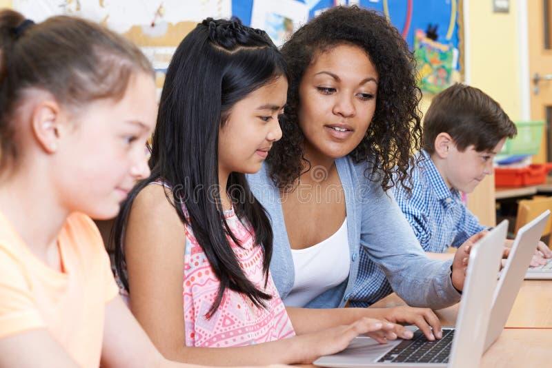 Alumnos elementales de Helping Group Of del profesor en ordenador fotografía de archivo