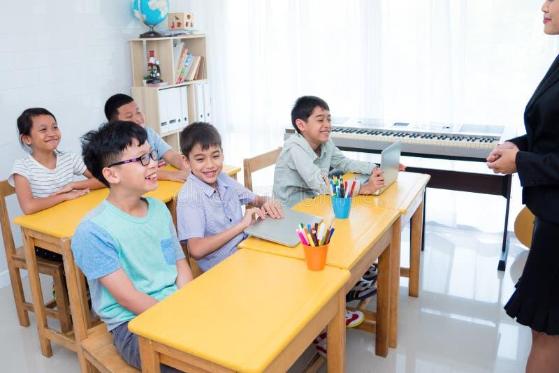 Alumnos elementales que sonríen feliz en sala de clase foto de archivo