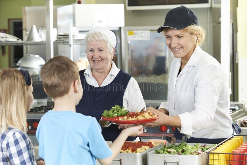 Alumnos en la cafetería de la escuela que es servida el almuerzo por las señoras de la cena fotografía de archivo