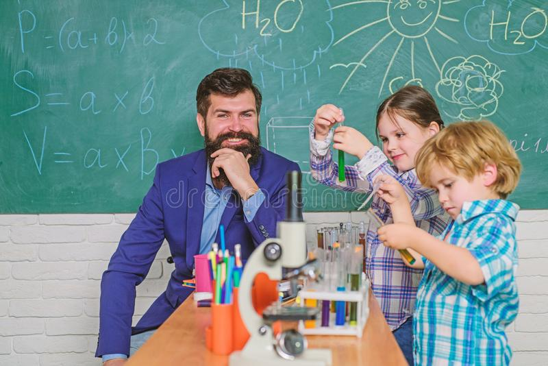 Alumnos en la clase de qu?mica De nuevo a escuela Concepto educativo profesor feliz de los ni?os fabricaci?n de los cient?ficos d imagenes de archivo