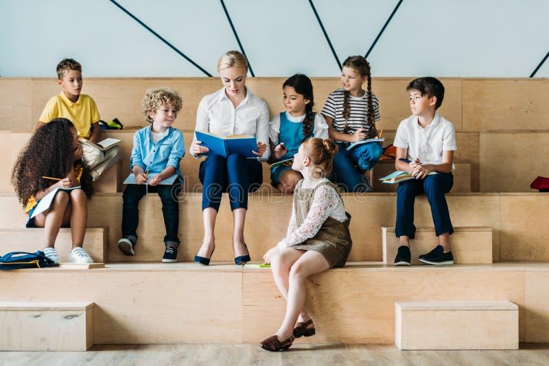 alumnos felices adorables que escuchan su profesor mientras que se sienta imagenes de archivo