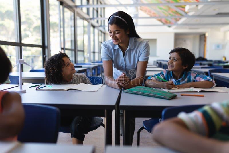 Alumnos felices que hablan con el profesor en el escritorio en sala de clase imagen de archivo