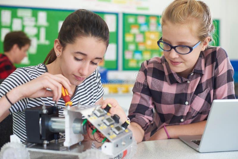 Alumnos femeninos en la lección de la ciencia que estudian la robótica imagenes de archivo
