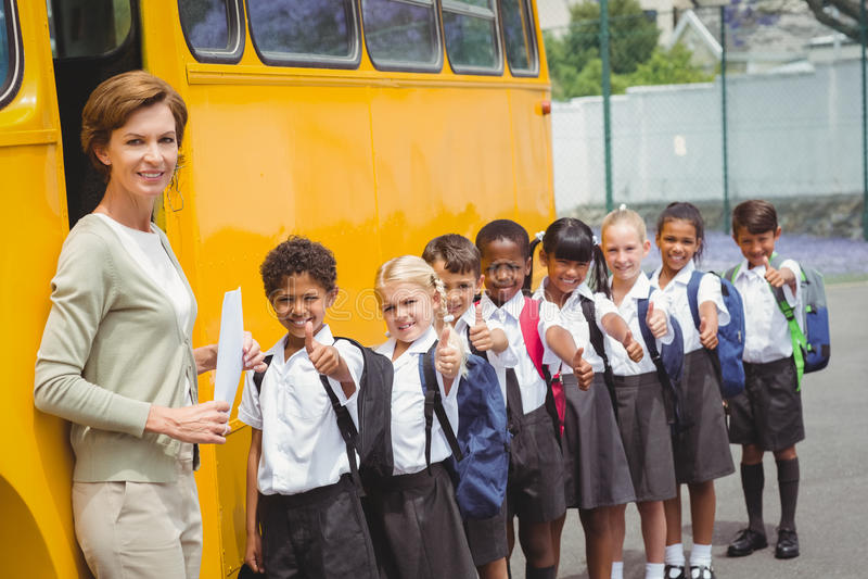 Alumnos lindos que esperan para conseguir en el autobús escolar imagen de archivo libre de regalías