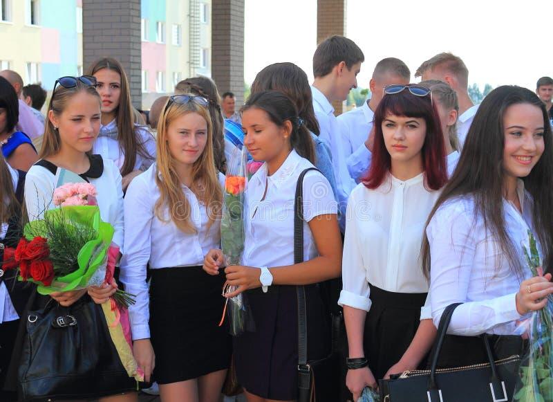Alumnos mayores de las muchachas en una regla solemne el 1 de septiembre fotos de archivo