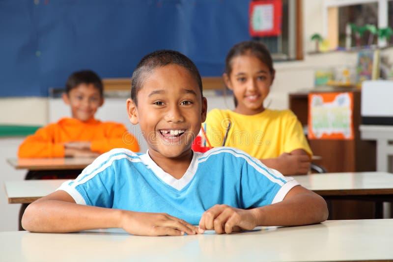 Alumnos primarios alegres en sala de clase imagen de archivo