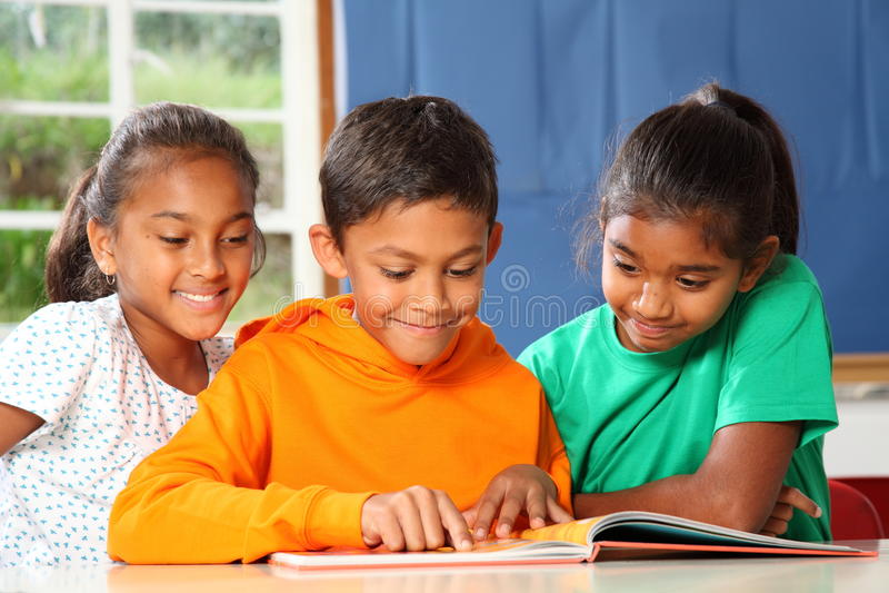 Alumnos primarios en el aprendizaje de la lectura de la clase foto de archivo