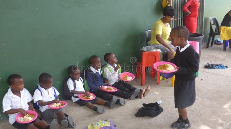 Alumnos que almuerzan en una escuela en Suráfrica i imagen de archivo libre de regalías