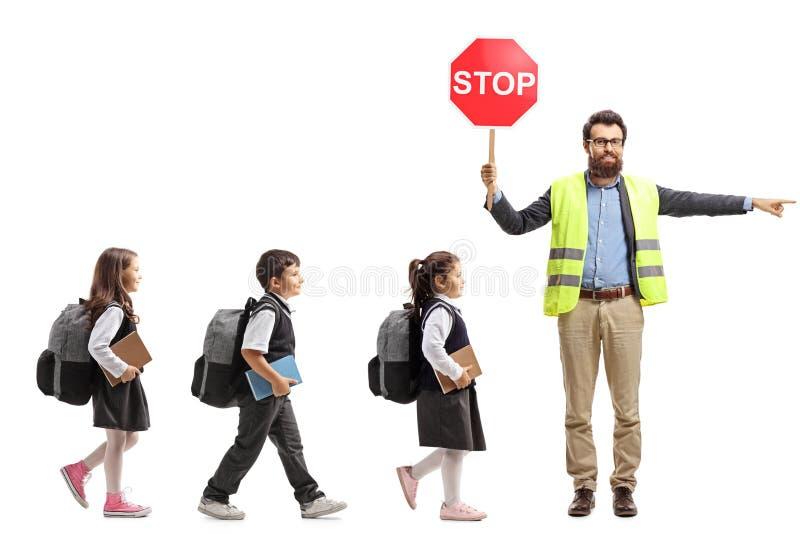 Alumnos que caminan en una línea y un profesor con el chaleco de la seguridad imagen de archivo