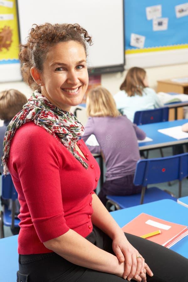 Alumnos que estudian en sala de clase con el profesor foto de archivo