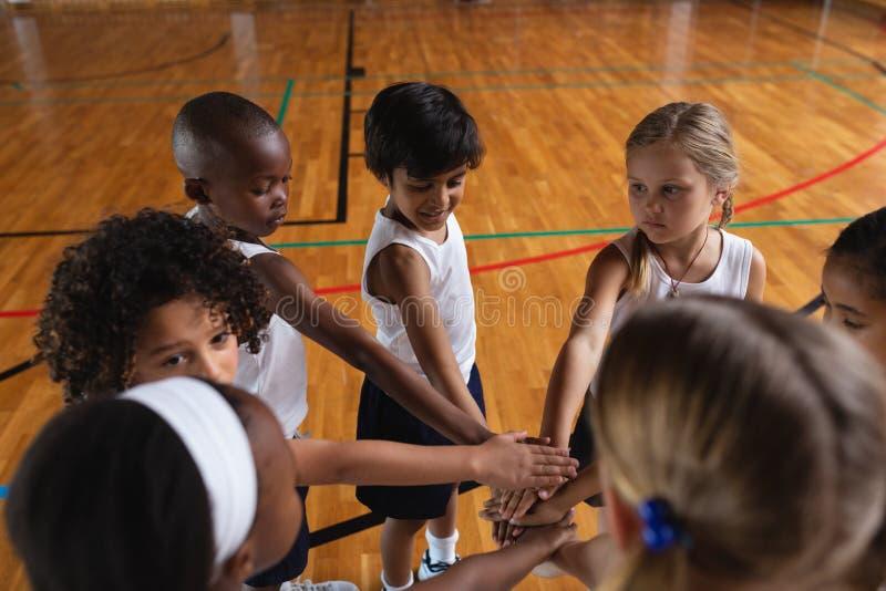 Alumnos que forman la pila de la mano en la cancha de básquet foto de archivo libre de regalías