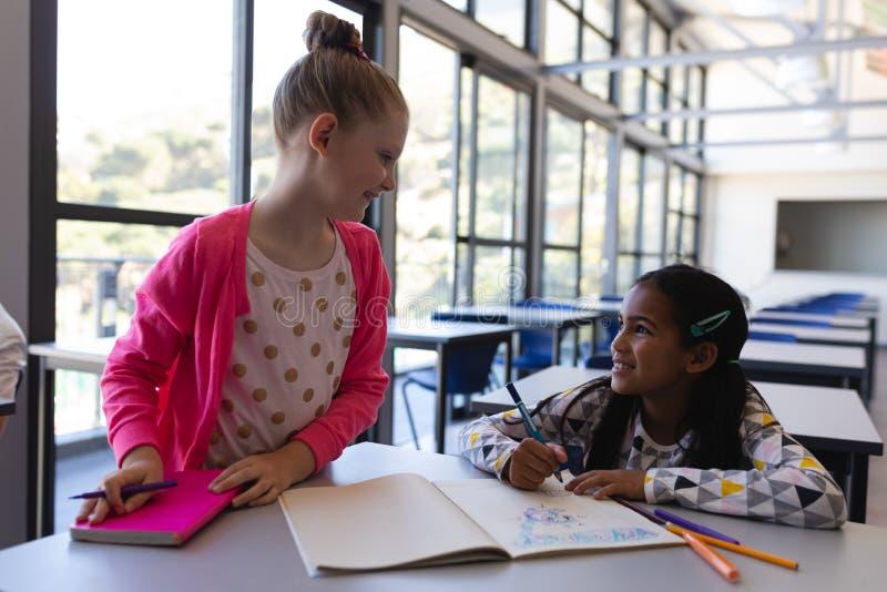 Alumnos que hablan con uno a en el escritorio en sala de clase fotos de archivo