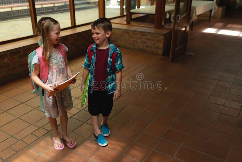 Alumnos que hablan con uno a en pasillo de la escuela primaria foto de archivo libre de regalías