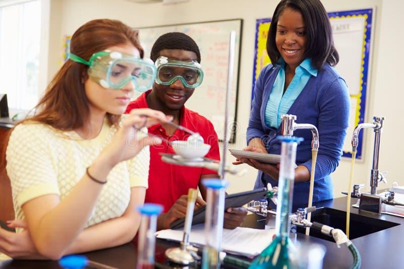 Alumnos que realizan el experimento en clase de la ciencia imágenes de archivo libres de regalías