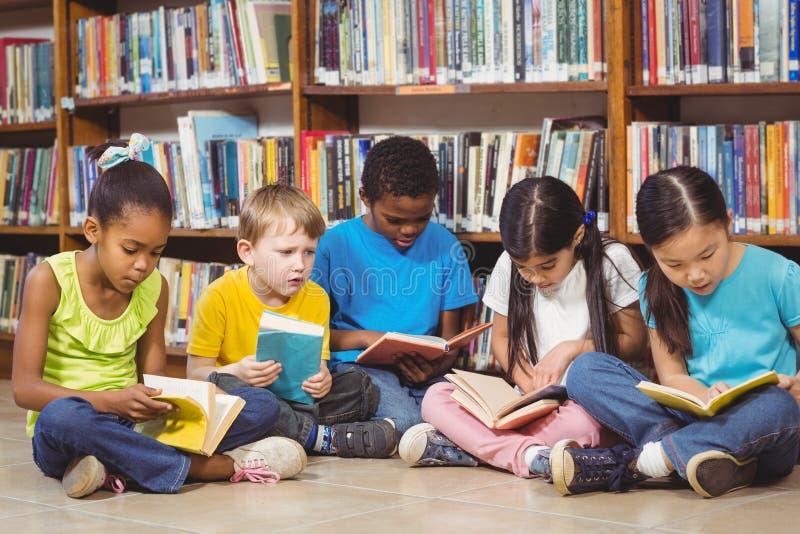Alumnos que se sientan en la tierra y los libros de lectura en la biblioteca fotos de archivo
