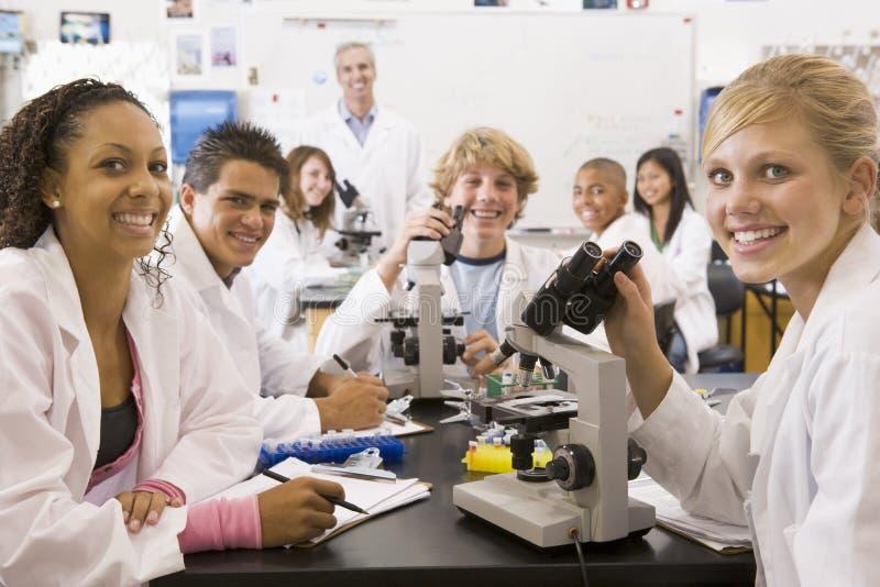 Alumnos y su profesor en clase de la ciencia fotos de archivo