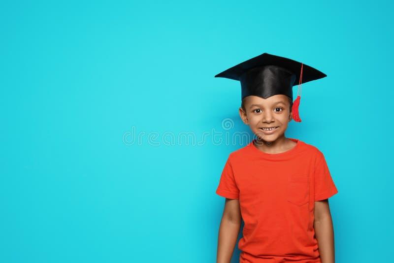 Aluno afro-americano pequeno com tampão graduado fotografia de stock