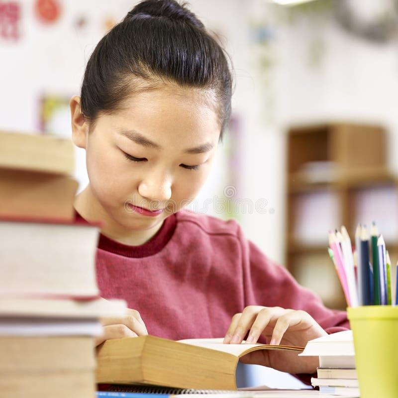 Aluno asiático da escola primária que lê um livro na sala de aula fotografia de stock