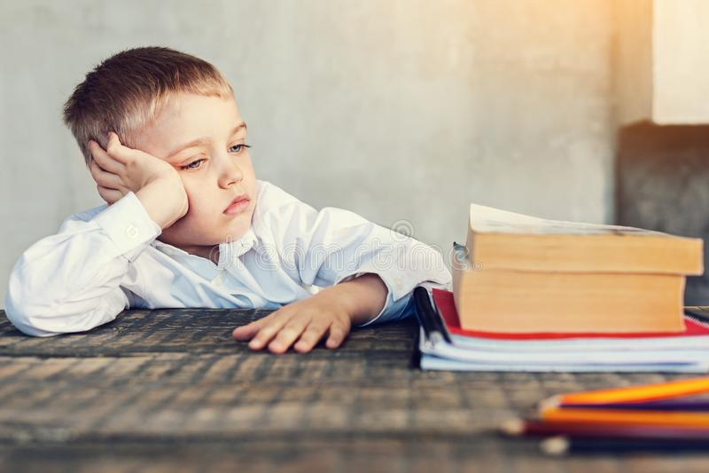 Aluno cansado pequeno que olha seus livros fotos de stock