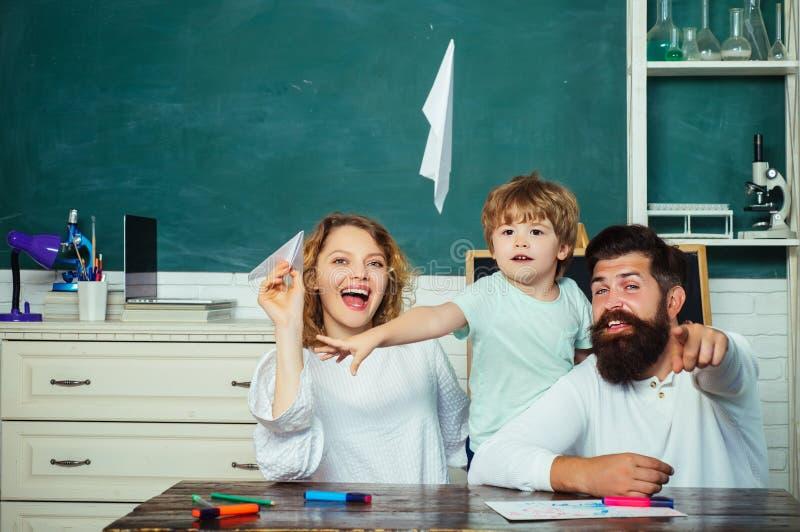 Aluno com o avião de papel que joga com pais Pai e filho da mãe que educam junto Educação para crianças fora de imagem de stock