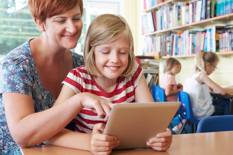 Aluno da escola com o computador de Using Digital Tablet do professor na classe fotos de stock