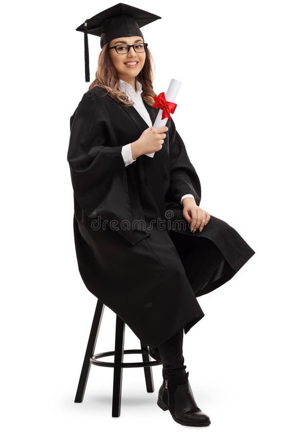 Aluno diplomado fêmea com um diploma que senta-se em uma cadeira e em uma manutenção programada fotografia de stock royalty free