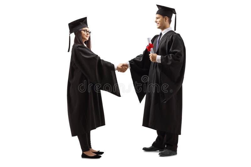 Aluno diplomado fêmea e aluno diplomado masculino que agita as mãos fotos de stock
