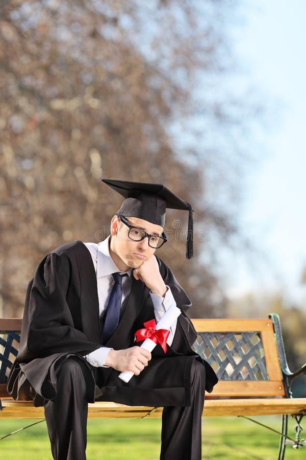 Aluno diplomado preocupado que senta-se no banco no parque fotos de stock