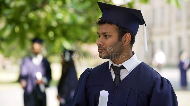 Aluno diplomado que olha na distância, ninguém que felicita o, solidão fotografia de stock